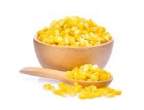 在木在白色隔绝的碗和匙子的甜玉米 免版税库存图片