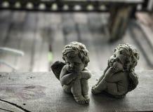 在木地板上的丘比特雕塑 库存图片