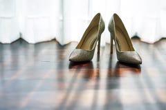 在木地板上的妇女` s鞋子与在地板,在白色帷幕后的太阳光-低角度上的阴影 免版税库存照片