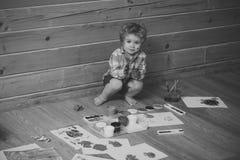 在木地板上的年轻艺术家男孩画家绘画 图库摄影