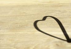 在木地板上的心形的阴影 库存图片