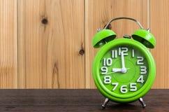 在木地板上的时钟有木背景 库存图片