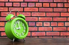 在木地板上的时钟有砖墙背景 免版税库存图片