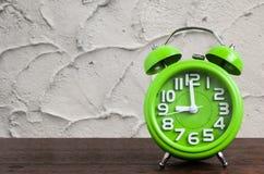 在木地板上的时钟有水泥背景 免版税图库摄影