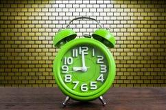 在木地板上的时钟有黄色砖墙背景 免版税库存图片