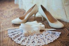 在木地板上的白色新娘鞋子 免版税库存照片
