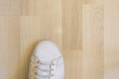 在木地板上的白色运动鞋鞋子 免版税库存照片