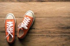 在木地板上的红色运动鞋 -生活方式 库存照片