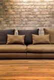 在木地板上的美丽的棕色织品沙发与砖墙 库存图片