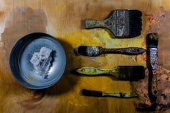 在木地板上的老脏的画笔 库存图片