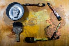 在木地板上的老脏的画笔 库存照片