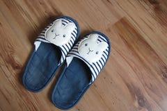 在木地板上的蓝色小兔拖鞋 库存图片