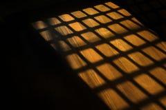 在木地板上的黑暗的窗户栏阴影在监狱 免版税库存图片