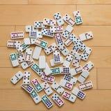 在木地板上延长的五颜六色的多米诺 库存图片