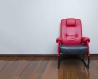 在木地板内部的现代红色和黑皮椅沙发 免版税库存照片