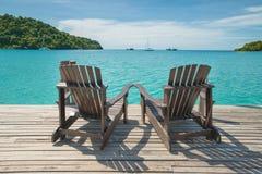 在木地板安置的两张海滩睡椅在海视图 免版税库存照片