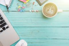 在木地板柔和的淡色彩的计算机膝上型计算机运作的书桌概念 免版税库存照片
