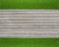 在木地板背景的绿草 图库摄影