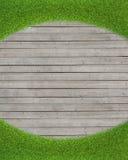 在木地板背景的绿草 免版税库存照片