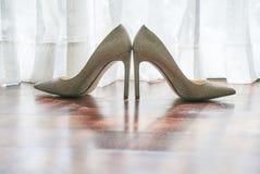 在木地板,在白色帷幕,鞋子的阴影后的太阳光上的妇女` s鞋子在地板-低角度上的 图库摄影