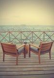 在木地板(被过滤的图象被处理的vinta上的两张海滩睡椅 免版税库存照片