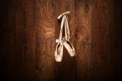 在木墙壁上垂悬的芭蕾舞鞋 库存图片