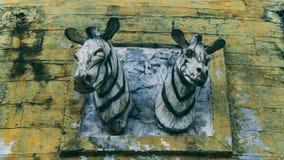 在木墙壁上的两个木斑马头在公共场所 库存照片