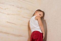 在木墙壁上的害羞的逗人喜爱的小男孩 免版税库存照片