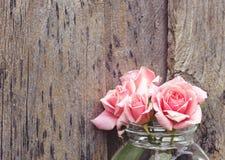 在木墙壁上的桃红色玫瑰 库存图片