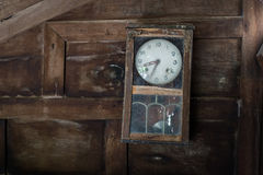 在木墙壁上的残破的摆钟 库存图片