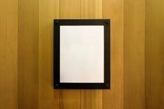 在木墙壁上的白色空白的空的棕色照片框架 背景,墙纸 免版税图库摄影