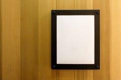 在木墙壁上的白色空白的空的棕色照片框架 背景,墙纸 库存照片