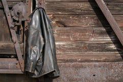 在木墙壁上的皮夹克 免版税库存图片