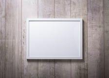 在木墙壁上的空白的白色画框 免版税库存照片
