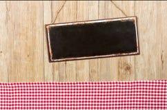 在木墙壁上的空的金属标志有方格的装饰的 免版税库存照片