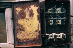在木墙壁上的老打破的交换机 被拆卸的,被掠夺的电子交换机 盾,设备operat控制板  免版税库存照片