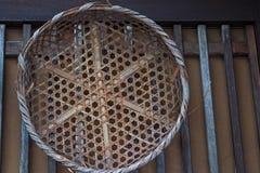 在木墙壁上的老竹柳条筐 库存图片