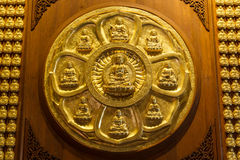 在木墙壁上的金黄中国菩萨在泰国 免版税库存照片