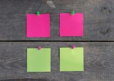 在木墙壁上的紫色和绿色贴纸 免版税库存图片