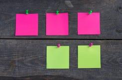 在木墙壁上的紫色和绿色贴纸 图库摄影