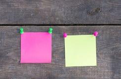 在木墙壁上的紫色和绿色贴纸 库存图片