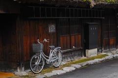 在木墙壁旁边的经典自行车公园在日本 免版税库存照片
