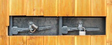 在木墙壁的孔有在一个灰色金属门的两挂锁的 库存照片