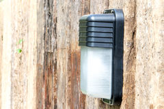 在木墙壁的灯 免版税库存图片