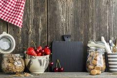 在木墙壁的背景的简单的厨房静物画在一个架子的与利器、工具,大理石碗和草莓 免版税库存图片