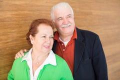 在木墙壁背景的愉快的退休的夫妇 图库摄影