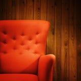 在木墙壁附近的经典红色扶手椅子 图库摄影