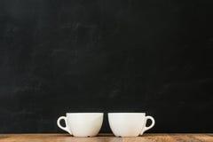 在木头一起安排的两个加奶咖啡杯子 库存照片