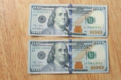 在木头后面地面的一百元钞票 库存图片
