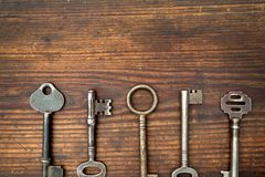 在木头安排的老钥匙 免版税库存图片